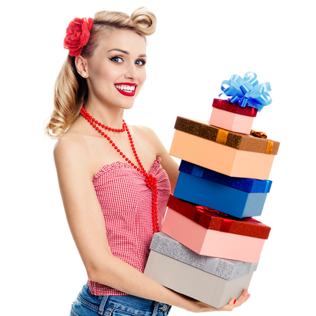 upsweep: Portrait of beautiful young happy woman in pin-up style clothing, holding gift boxes, isolated over white. Caucasian blond model posing in retro fashion and vintage concept shoot.