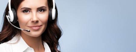 Portrait of cheerful customer support female phone operator in headset, against grey background. Consulting and assistance service call center. Banque d'images