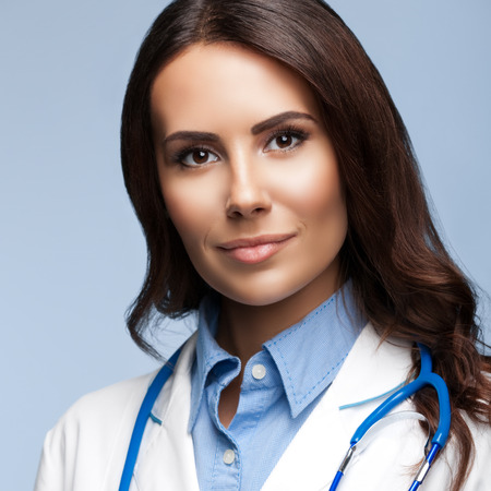 Portrait of happy smiling young female doctor, on grey background