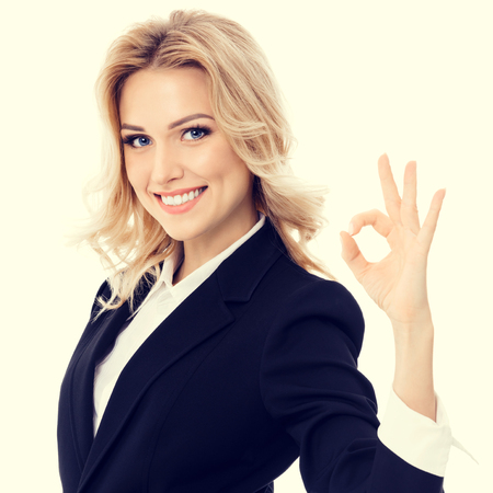 a ok: Happy smiling beautiful young businesswoman showing okay gesture
