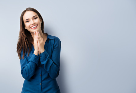 jovenes felices: Retrato de gesticular feliz de la mujer joven sonriente en la ropa azul informal elegante, de color gris, con área de copyspace de texto o lema
