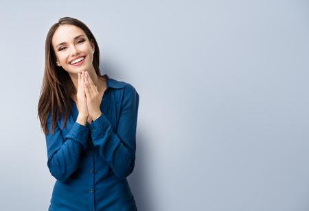 Ritratto di felice gesticolare giovane donna sorridente in vestiti blu casual elegante, sul grigio, con area copyspace per testo o uno slogan Archivio Fotografico