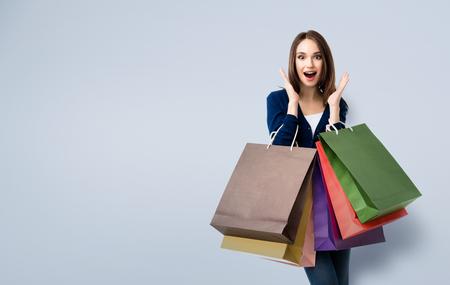 テキストまたはスローガンの copyspace エリアと、ショッピング バッグにカジュアル衣料に非常に満足している美しい若い女性