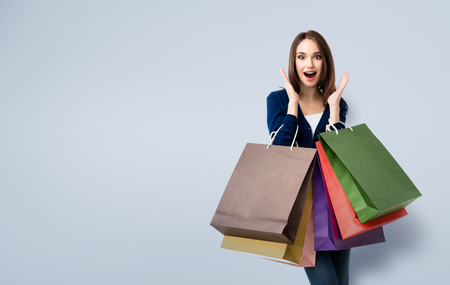 Muy feliz hermosa mujer joven en ropa casual con bolsas de la compra, con área de copyspace de texto o lema Foto de archivo - 59131382