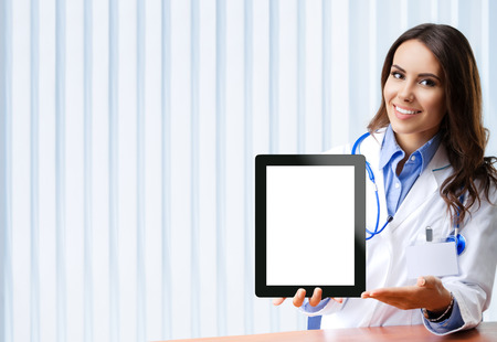areas: Portrait of happy smiling young female doctor showing no-name tablet pc with blank copyspace area for slogan or text, at office. Stock Photo