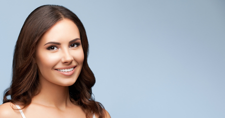 young woman smiling: Portrait of happy smiling young beautiful woman in white casual clothing, over grey background, with blank copyspace area