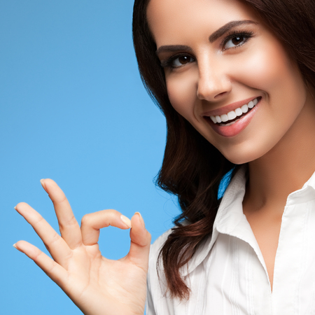 allright: Portrait of happy smiling young cheerful businesswoman, showing okay hand sign gesture, on blue
