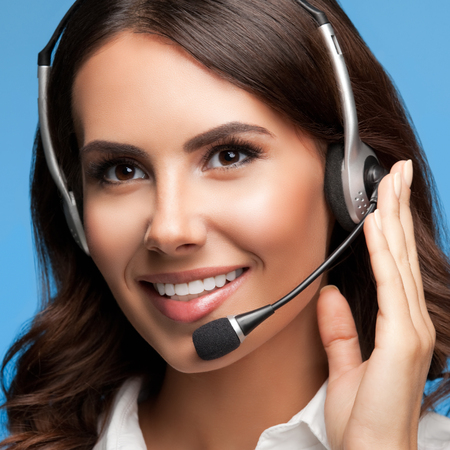 handsfree telephone: Portrait of cheerful customer support female phone operator in headset, over blue background Stock Photo