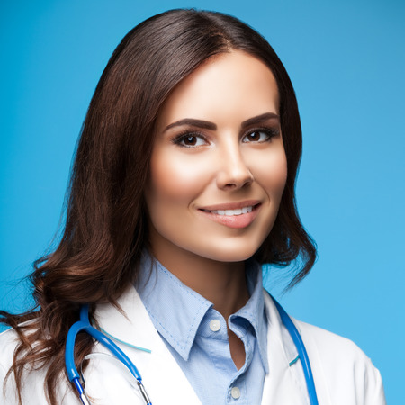 Portrait of happy smiling female doctor, on blue background Stock Photo