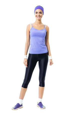 background person: Full body portrait of smiling sporty brunette woman in violet sportswear, isolated against white background. Young female fitness instructor or personal trainer at studio shot.