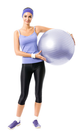 Full body portrait of happy smiling woman holding pilates ball, in violet sportswear, isolated against white background. Young sporty dark-haired model at studio shot. Health, beauty and fitness concept.
