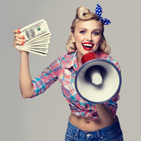 good grooming: Portrait of beautiful young happy smiling woman with money and megaphone, dressed in pin-up style. Caucasian blond model posing in retro fashion and vintage concept studio shoot.