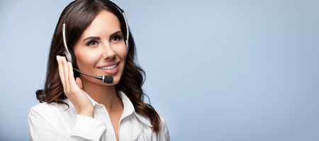 customer: Customer support female phone operator in headset, with copyspace, on grey background. Consulting and assistance service call center.