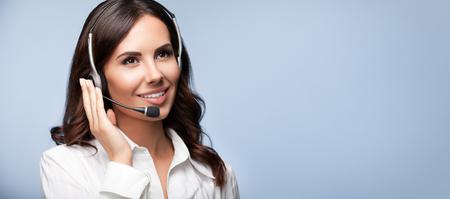 Soutien à la clientèle de l'opérateur femelle de téléphone dans le casque, avec copyspace, sur fond gris. Conseils et services d'assistance du centre d'appels. Banque d'images