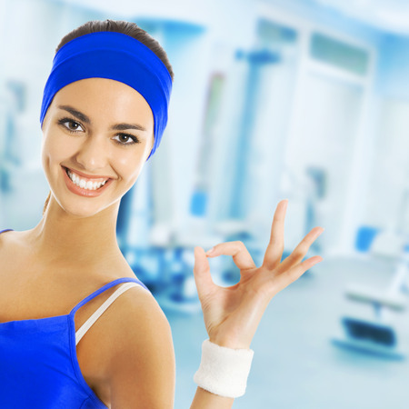 gesturing: Young happy woman in sports wear gesturing, at fitness club or center
