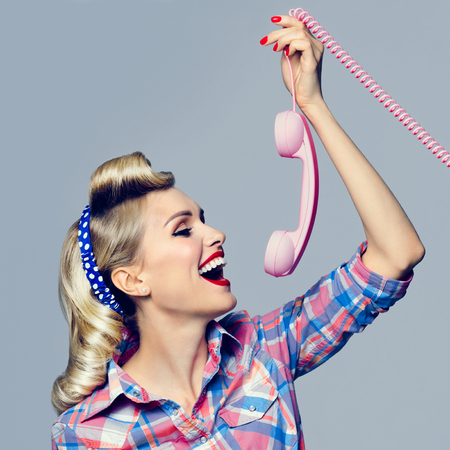 Portrait of beautiful young happy woman with phone, dressed in pin-up style. Caucasian blond model posing in retro fashion and vintage concept studio shoot.