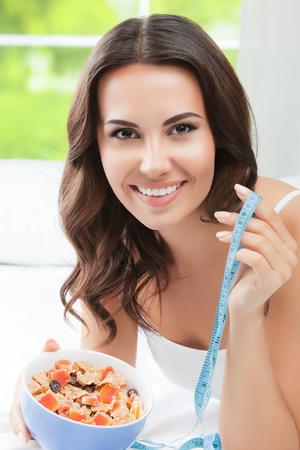 cinta metrica: La mujer alegre morena con muselina y cinta de la medida, en el interior. alimentación saludable, la belleza y el concepto de dieta. Foto de archivo
