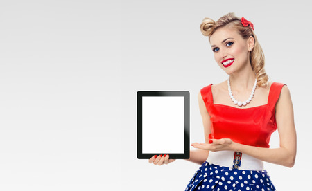 Woman, showing blank no-name tablet pc monitor, with copyspace, dressed in pin-up style dress in polka dot, on grey background, with blank copyspace area for text or slogan. Caucasian blond model posing in retro fashion vintage shoot.