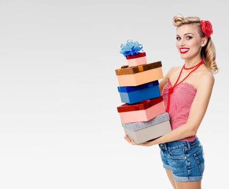 upsweep: Portrait of beautiful young happy smiling woman in pin-up style clothing, holding gift boxes, on grey background, with blank copyspace area for text or slogan. Caucasian blond model posing in retro fashion and vintage concept shoot.