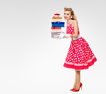 Full body of happy woman in pin-up style red dress in polka dot and white gloves, holding gift boxes, on grey background, with blank copyspace area for text or slogan. Caucasian blond model posing in retro fashion and vintage shoot.