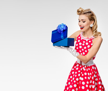 Portrait of beautiful young happy woman dressed in pin-up style red dress in polka dot and white gloves, on grey background, with blank copyspace area for text or slogan. Caucasian blond model posing in retro fashion studio shoot. Stock Photo