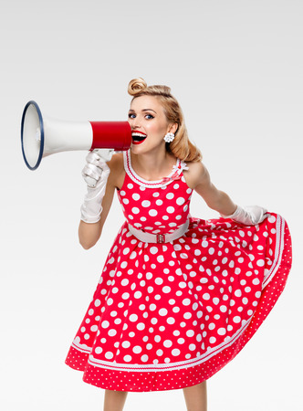 Portrait of woman holding megaphone, dressed in pin-up style red dress in polka dot and white gloves, on grey background. Caucasian blond model posing in retro fashion vintage studio shoot. Stock Photo