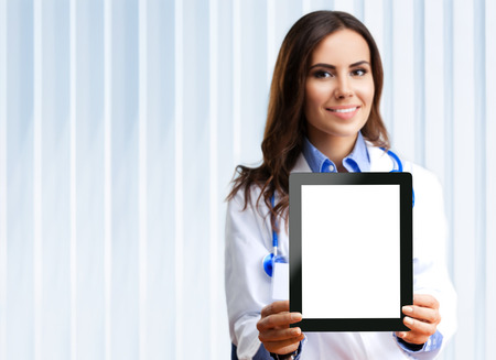 Portrait of happy smiling young female doctor showing no-name tablet pc with blank copyspace area for slogan or text, at office. Selective focus on tablet pc.