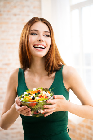 eating salad: Portrait of happy smiling young woman with vegetarian vegetable salad, indoors or at home. Beauty and dieting concept. Weight lossing, by healthy eating.