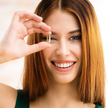 model fish: Portrait of smiling young woman with Omega 3 fish oil capsule, indoors. Health care and medical concept with caucasian beautiful model. Square composition.
