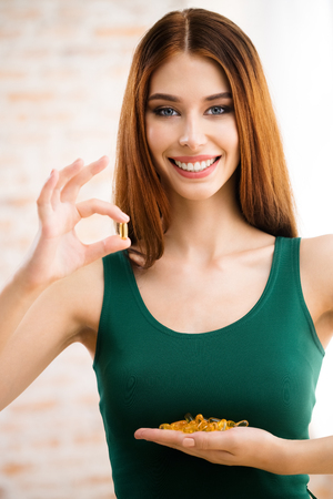 fish oil: Portrait of smiling young woman with Omega 3 fish oil capsule, indoors. Health care and medical concept with caucasian beautiful model. Stock Photo