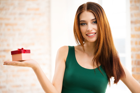 looking for love: Young happy smiling woman with gifts, at home, indoors. Celebration and holiday sale concept with caucasian beautiful model.