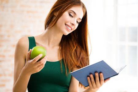 clothes organizer: Happy smiling young woman reading book or organizer, with green apple at home, indoors. Caucasian beautiful brunette model in education concept shoot. Stock Photo