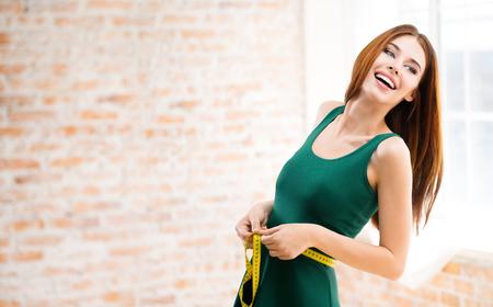 cintura: feliz mujer joven que mide su cintura con una cinta métrica, en casa, en el interior. Modelo caucásico en el estilo de vida saludable, la dieta y el concepto de belleza rodaje. área de copyspace en blanco para lema o mensaje de texto.