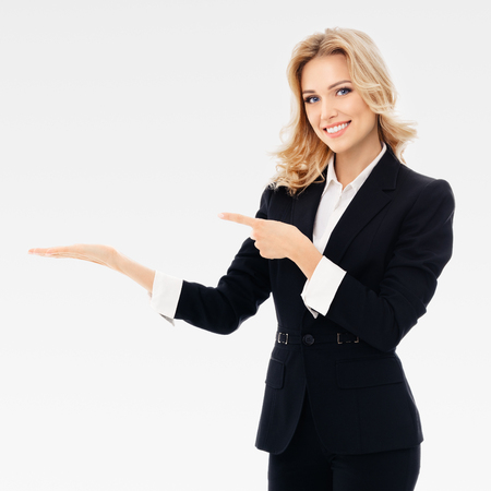 Portrait of smiling young cheerful businesswoman, showing something or blank copyspace area for slogan or text message, on grey background. Caucasian blond model in business presentation or sales advertision concept. Square composition.