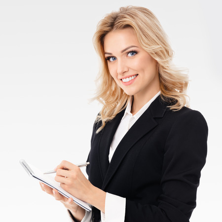 Portrait of young beautiful businesswoman with clipboard writing, on grey background. Caucasian blond model in business presentation or sales advertision concept.  Square composition.