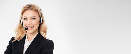 superficie: Portrait of happy smiling young support phone operator or businesswomen in headset, on grey background, with blank copyspace area for slogan or text message. Foto de archivo