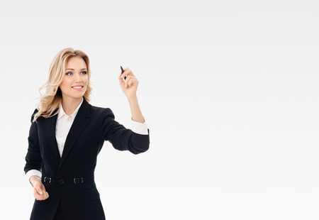 glassboard: Happy smiling cheerful young businesswoman writing or drawing something on screen or transparent glass, by blue marker, on grey background. Caucasian blond model in business presentation or sales advertision concept.