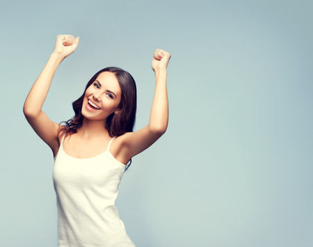Portrait of cheerful gesturing smiling young woman, with blank copyspace area for slogan or text message. Caucasian brunette model in emotional concept studio shoot.
