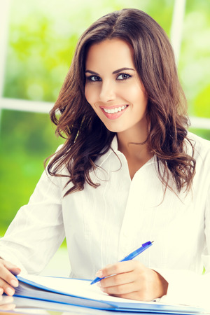 Portrait of young happy businesswoman at office. Caucasian brunette model in business concept shoot.