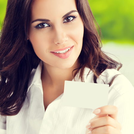 Happy smiling brunette businesswoman showing blank business or plastic card with copyspace area for slogan or text. Invitation concept.