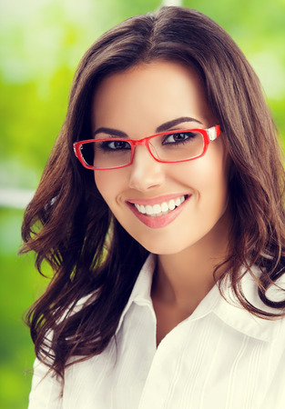 Portrait of young smiling businesswoman in glasses. Caucasian brunette model in business concept shoot.
