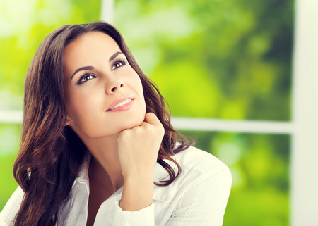 woman looking: Thinking smiling attractive businesswoman looking up, at office, with blank copyspace area for slogan or text. Caucasian brunette model in business concept shoot. Stock Photo