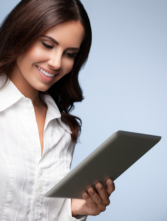 Portrait of happy smiling beautiful young businesswoman using no-name tablet pc, over grey background. Caucasian brunette model in business concept shoot.