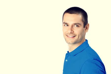 Portrait of happy smiling young man. Caucasian young male hansome brunette model in blue casual clothing in studio shoot. Blank copyspace area for advertising slogan or text message. Stock Photo