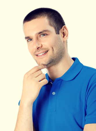 one man only: Portrait of happy smiling young man. Caucasian young male hansome brunette model in blue casual clothing in studio shoot. Stock Photo