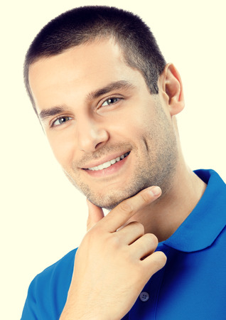 Portrait of happy smiling young man. Caucasian young male hansome brunette model in blue casual clothing in studio shoot. Stock Photo