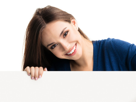 sho: Portrait of happy smiling young woman in blue casual smart clothing, showing empty blank signboard with copyspace area for text or slogan, isolated against white backgroundCaucasian brunette model in advertising, pr, marketing and presentation concept sho