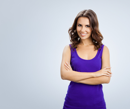 Portrait of young cheerful smiling woman, over grey background. Blank copyspace area for advertising slogan or text message. Caucasian brunette model in emoshions and optimistic, positive, happy feeling concept studio shoot.