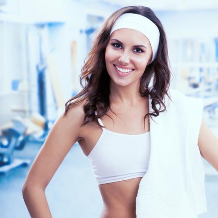 mujer sola: mujer sonriente Happpy en el club de fitness o gimnasio. deportes individuales, capacitación, entrenamiento, ejercicio, aeróbicos y el concepto de estilo de vida saludable. mujer instructor. Plaza de la composición.