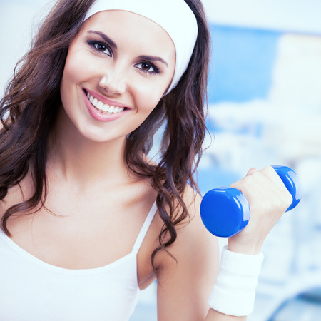 gimnasia aerobica: Joven mujer feliz en la aptitud al desgaste ejercicio con pesas, en el gimnasio o en el gimnasio. deportes individuales, capacitación, entrenamiento, ejercicio, aeróbicos y el concepto de estilo de vida saludable. mujer instructor. Plaza de la composición.